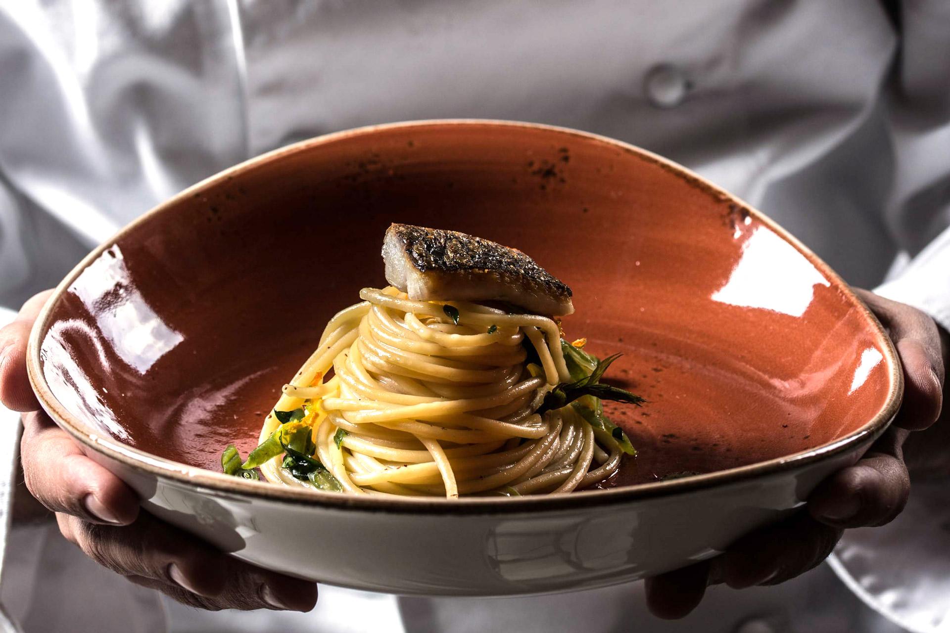 Piatto di spaghetti con branzino e asparagi verdi